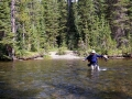 Backpacker crossing the Bechler River